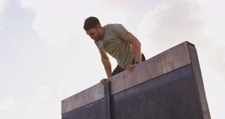 konkurenti : Front view of a young Caucasian man vaulting over a wall at an outdoor gym during a bootcamp training session