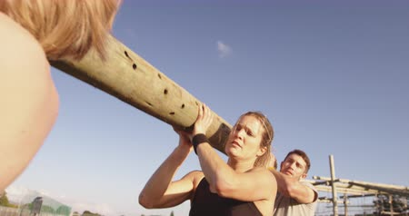 проведение : Front view close up of two young Caucasian women and a young Caucasian man carrying a log of wood togther and raising over their heads as they walk, at an outdoor gym during a bootcamp training session