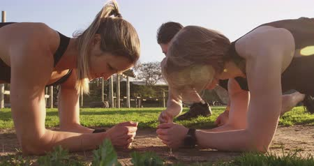 achievements : Side view close up of two young Caucasian women doing the plank exercise with a young Caucasian male trainer kneeling and instructing them at an outdoor gym during a bootcamp training session Stock Footage