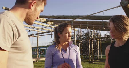 cronômetro : Side view of a young Caucasian woman and a young Caucasian man listening to a young Caucasian female trainer holding a clipboard giving them feedback at an outdoor gym during a bootcamp training session Stock Footage