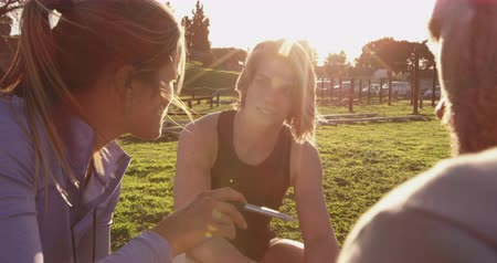 cronômetro : Over the shoulder view of a young Caucasian woman and a young Caucasian man listening to a young Caucasian female trainer holding giving them feedback sitting on the grass at an outdoor gym during a bootcamp training session, backlit by sunlight