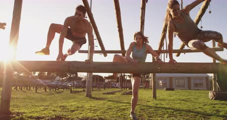 arranque : Front view of two young Caucasian women and a young Caucasian man vaulting over a hurdle at an outdoor gym during a bootcamp training session Vídeos