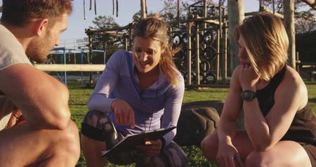 cronômetro : Front view of a young Caucasian woman and a young Caucasian man listening to a young Caucasian female trainer holding a clipboard giving them feedback kneeling at an outdoor gym during a bootcamp training session