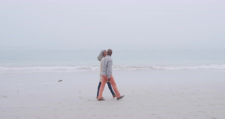 companionship : Side view of a mature mixed race couple holding hands and walking on a beach by the sea Stock Footage