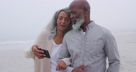 companionship : Front view close up of a mature mixed race couple walking arm in arm and taking a selfie on a beach by the sea
