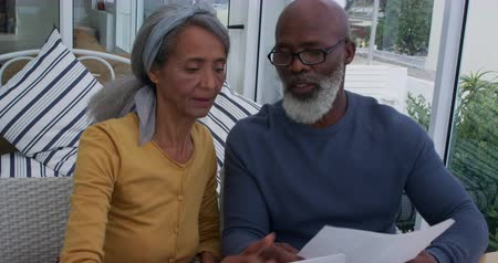 companionship : Front view close up of a mature mixed race couple using a laptop computer, looking at a document and talking at home Stock Footage