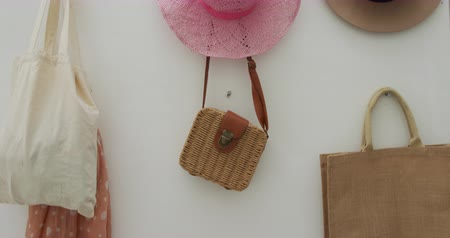 sunhat : Sun hats and handbags hanging on a wall