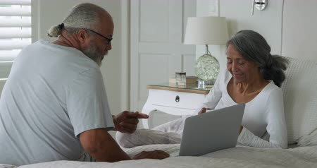draak : Side view of a mature mixed race couple using a laptop computer sitting on a bed at home