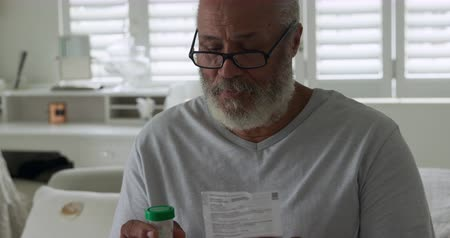 visszavonulás : Front view close up of a mature mixed race man reading a prescription and holding a bottle of medication at home