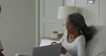 draak : Side view of a mature mixed race couple with a laptop computer sitting on a bed at home talking Stockvideo