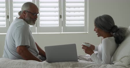 baardagaam : Side view of a mature mixed race couple using a laptop computer and talking in their bedroom at home Stockvideo