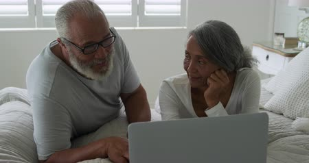 companionship : Front view close up of a mature mixed race couple using a laptop computer in their bedroom at home
