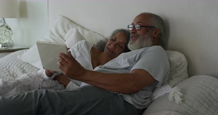 reclináveis : Side view of a mature mixed race couple using a tablet computer lying in bed at home