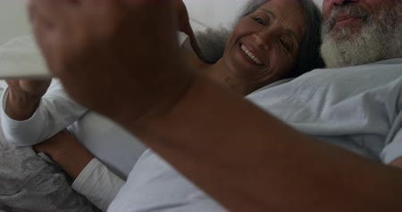 reclináveis : Front view close up of a mature mixed race couple using a tablet computer lying in bed at home