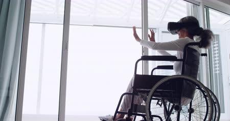paraplegic : Side view of a mature mixed race woman in a wheelchair using a VR headset