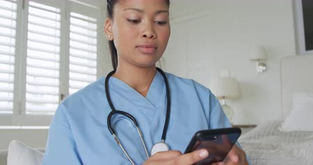 trabalhos domésticos : Front view close up of a young mixed race female nurse using a smartphone and relaxing on a bed