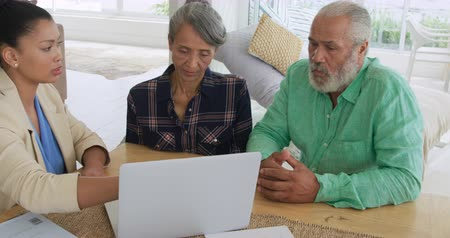 companionship : Front view close up of a mature mixed race couple meeting with a young mixed race female financial advisor at their home Stock Footage