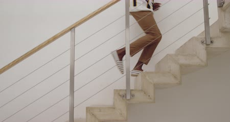 corrimão : Low section of a young adult mixed race man running up the staircase home
