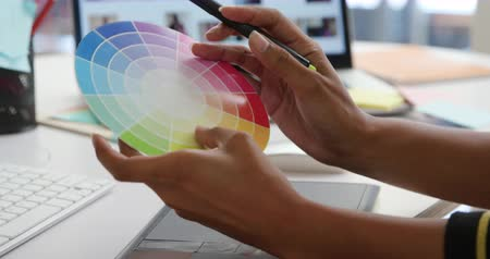 color swatch : Close up of hands of a young woman working in a modern creative office, using a graphics tablet choosing colours from a colour wheel Stock Footage