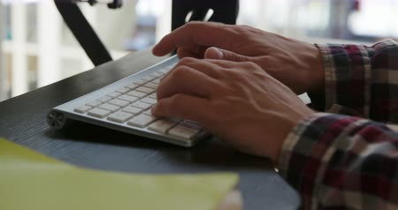 agência : Close up of hands of a young Caucasian male business creative working in a modern office, typing on a computer keyboard and mouse