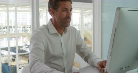 myszka komputerowa : Front view of a happy middle aged Caucasian male business creative working in a modern office, using a computer