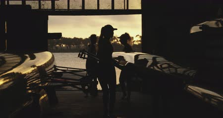 scull : Side view of a team of four young adult Caucasian female rowers on a river lifting a racing shell out of a boatshed before training on a river