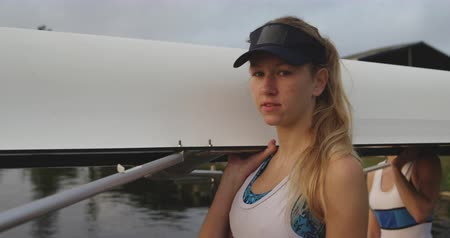 scull : Portrait of a young adult Caucasian female rower smiling to camera while carrying a racing shell with her teammates before training on a river Stock Footage