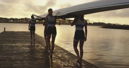 evezős : Rear view of a team of four young adult Caucasian rowers carrying a racing shell on their shoulders on a jetty before training on a river