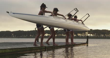 praca zespołowa : Side view of a team of four young adult Caucasian female rowers standing on a jetty and lowering a racing shell into a river before training