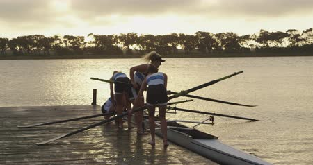 scull : Side view of a team of four young adult Caucasian female rowers standing on a jetty preparing oars and a racing shell for training on a river