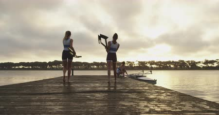 evezős : Rear view of two young adult Caucasian female rowers walking on a jetty carrying oars while their two teammates hold a racing shell on a river before training Stock mozgókép