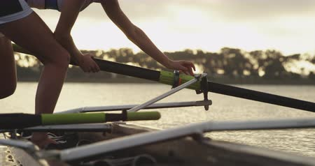 гребля : Side view of a young adult Caucasian female rower attaching an oar to a racing shell before training on a river
