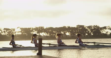 scull : Side view of a team of four young adult Caucasian women rowing in a racing shell on a river