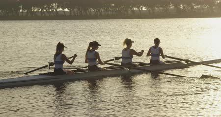scull : Side view of a team of four young adult Caucasian women rowing in a racing shell training on a river