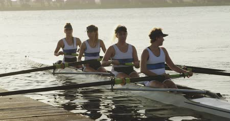 scull : Front view of a team of four young adult Caucasian women rowing in a racing shell on a river landing at a jetty