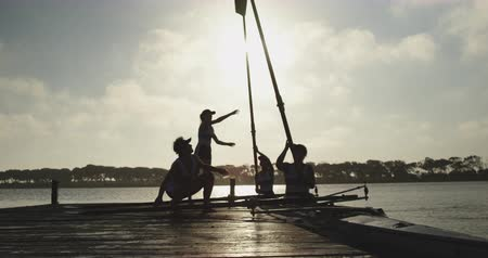 evezős : Front view of two young adult Caucasian female rowers in a racing shell on a river passing oars to their teammates on a jetty Stock mozgókép