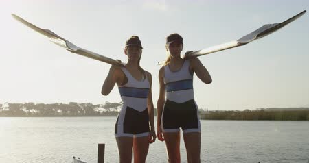 evezős : Portrait of two young adult Caucasian female rowers standing on a jetty by a river holding oars on their shoulders