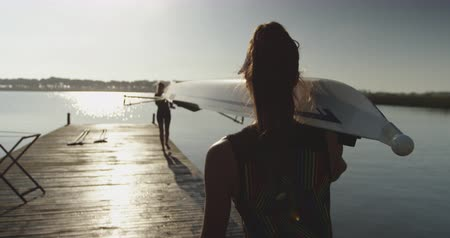 scull : Rear view of two young adult Caucasian female rowers carrying a racing shell on their shoulders on a jetty before training on a river
