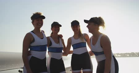 evezős : Portrait of a team of four young adult Caucasian female rowers wearing team colours standing with arms around each other smiling to camera by a river, backlit Stock mozgókép
