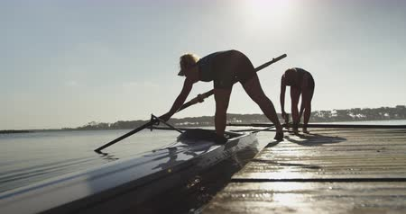 scull : Side view of two young adult Caucasian female rowers standing on a jetty preparing oars and a racing shell on a river before training
