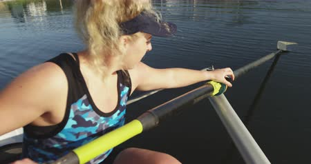 evezős : Side view close up of a young adult Caucasian female rower preparing oars and a racing shell on a river before training Stock mozgókép