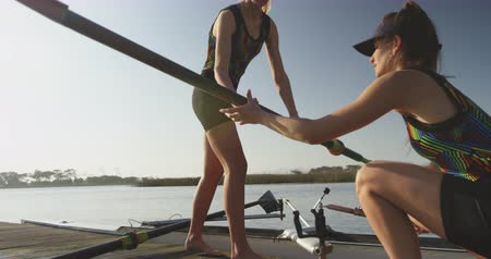 evezős : Side view of two young adult Caucasian female rowers preparing oars and a racing shell on a river before training