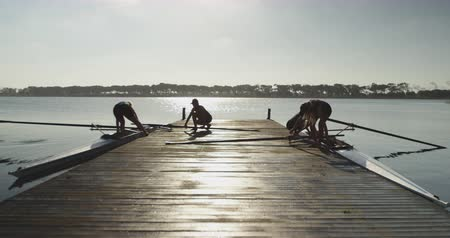 evezős : Side view of four young adult Caucasian women on a jetty preparing two racing shells on a river before training Stock mozgókép