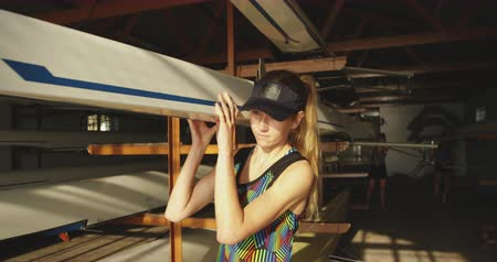 evezős : Front view of a young adult Caucasian female rower standing in a boatshed holding one end of a racing shell before training on a river