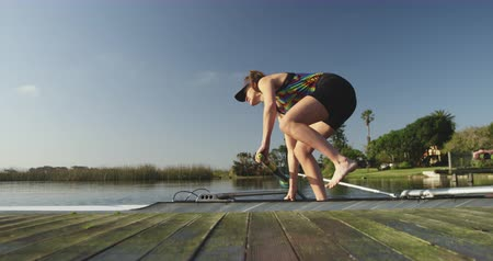 scull : Side view of a young adult Caucasian female rower standing in a racing shell with her teammate sitting in it and pushng it away from the jetty before training on a river