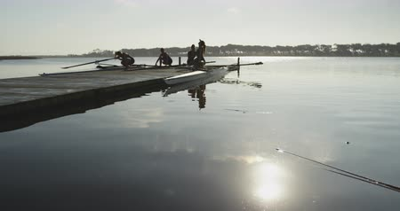 evezős : Side view of four young adult Caucasian female rowers preparing two racing shells on a river before training Stock mozgókép