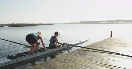 scull : Side view of two young adult Caucasian female rowers standing in a racing shell on a river pushing the boat away from the jetty before training