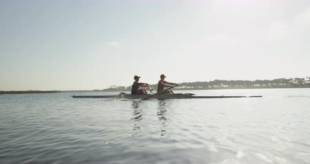 scull : Side view of two young adult Caucasian women rowing in a racing shell on a river during training Stock Footage