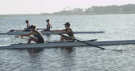 scull : Side view of a team of four young adult Caucasian women rowing in two racing shells on a river during training
