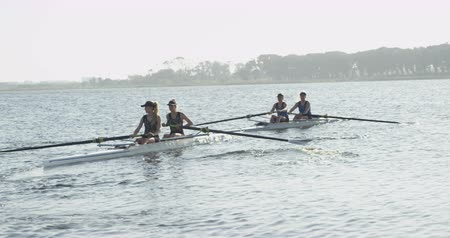 evezős : Side view of a team of four young adult Caucasian women rowing in two racing shells on a river during training